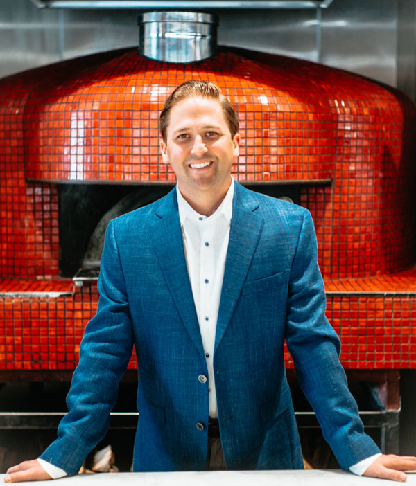 Jimmy Pardini in front of pizza oven