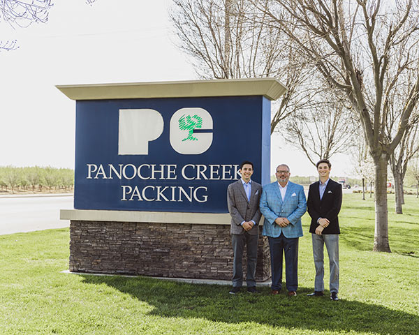 Frank Roque with sons in front of Panoche Packing sign